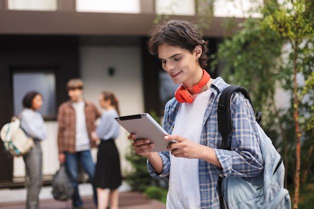 Porträt des jungen mannes mit roten kopfhörern und rucksack stehend und unter verwendung der tablette, während zeit im hof der universität mit studenten auf hintergrund verbringend