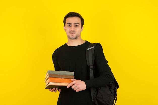 Porträt des jungen mannes mit rucksack, der bücher über gelber wand hält