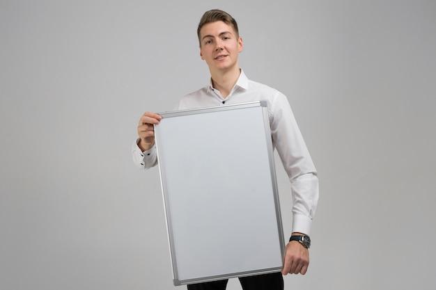 Porträt des jungen mannes mit sauberem magnettafel in seinen händen lokalisiert