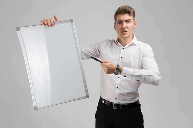 Porträt des jungen mannes mit sauberer magnettafel und markierung in seinen händen