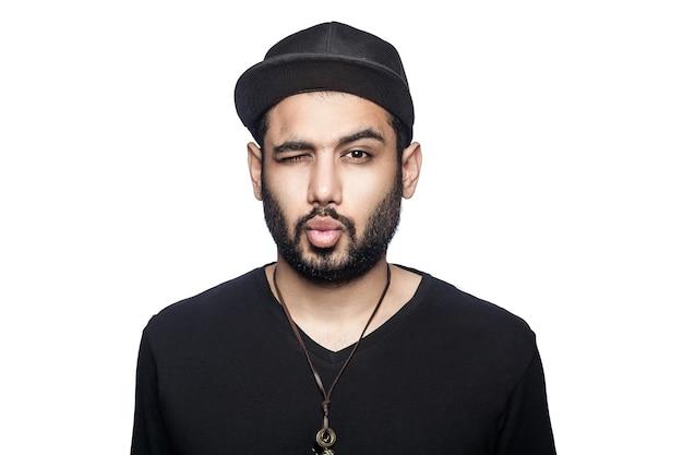 Porträt des jungen mannes mit schwarzem t-shirt und mütze, der die kamera mit augenzwinkern und kuss betrachtet. studioaufnahme, isoliert auf weißem hintergrund.