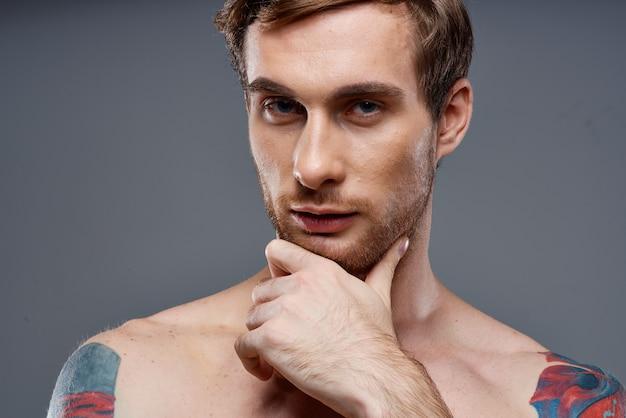 Porträt des jungen mannes mit tätowierungen auf grauem hintergrund und beschnittener ansicht des schönen gesichtsmodells