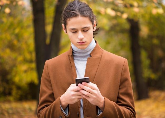 Porträt des jungen mannes sein telefon überprüfend