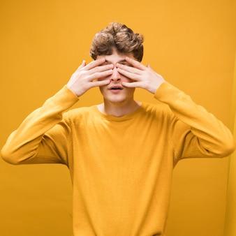 Porträt des jungen mannes seine augen in einer gelben szene bedeckend