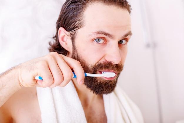 Porträt des jungen mannes seine zähne im badezimmer putzend