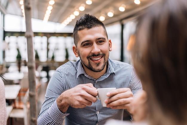 Porträt des jungen mannes sitzend an einem café und mit freund sprechend.