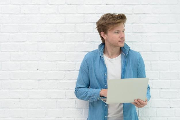 Porträt des jungen mannes stehend, laptop halten und medien mit glücklichem lächeln aufpassen