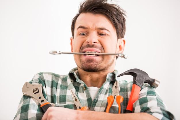 Porträt des jungen mannes tut reparatur zu hause mit werkzeugen.