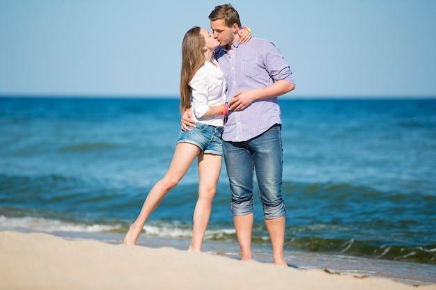 Porträt des jungen mannes und der frau, die auf einem strand küssen
