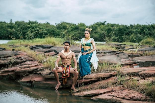 Porträt des jungen mannes und der frau, die schöne traditionelle kostümhaltung in der natur in thailand tragen