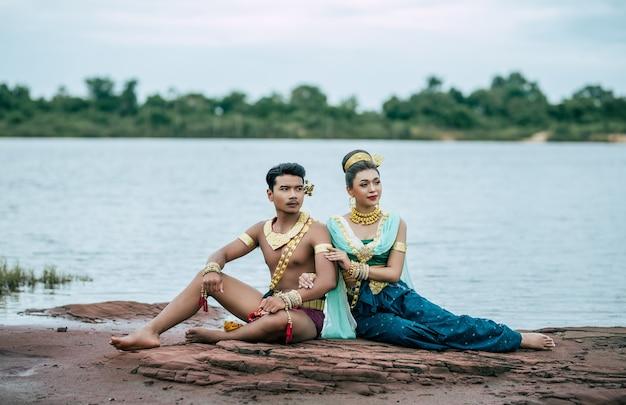 Porträt des jungen mannes und der frau, die traditionelles kostüm tragen, das in der natur in thailand aufwirft