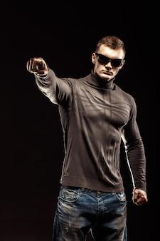 Porträt des jungen mannes zeigt einen finger, der auf schwarzer szene lokalisiert wird