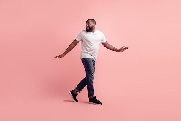Porträt des jungen mannes zu fuß zurückblicken auf leeren raum auf rosa hintergrund