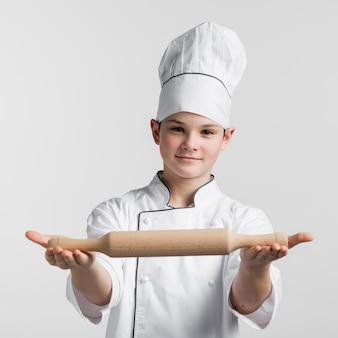 Porträt des jungen meisterkochs, der nudelholz hält