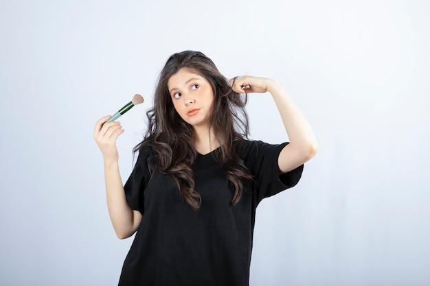 Porträt des jungen modells mit make-up mit pinsel stehend auf weißer wand.
