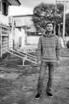 Porträt des jungen multiethnischen asiatischen mannes in den straßen draußen in schwarzweiss