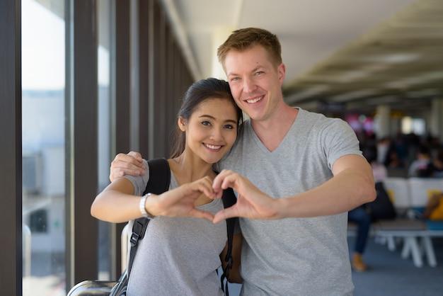 Porträt des jungen multiethnischen paares, das urlaub zusammen genießt