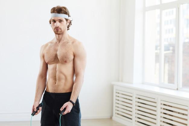Porträt des jungen muskulösen mannes, der kamera beim training mit springseil betrachtet