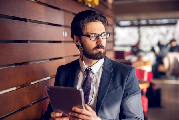 Porträt des jungen nachdenklichen gutaussehenden bärtigen geschäftsmannes im anzug, der musik von einem tablett in einem modernen café hört.