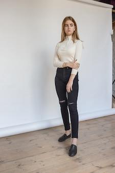 Porträt des jungen nachdenklichen jugendlichen modells, das weißen pullover und schwarze jeans trägt