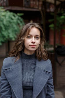 Porträt des jungen nachdenklichen mädchens im grauen mantel und im rollkragenpullover, der draußen aufwirft