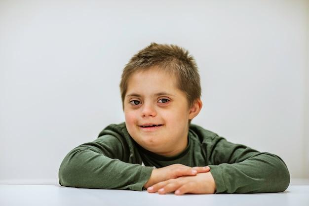Porträt des jungen niedlichen jungen mit down-syndrom, der am weißen tisch sitzt
