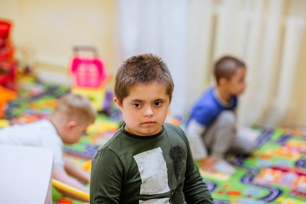 Porträt des jungen niedlichen jungen mit down-syndrom, der unter anderen kindern spielt.