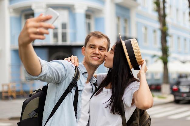Porträt des jungen paares, das ein selfie im freien nimmt