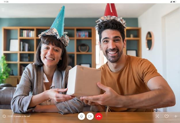 Porträt des jungen paares, das geburtstag auf einem videoanruf mit geschenkbox von zu hause feiert. neues normales lifestyle-konzept.
