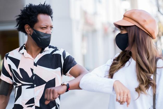 Porträt des jungen paares, das gesichtsmaske trägt und sich mit ihren ellbogen gegenseitig klopft, um hallo zu sagen, während sie draußen stehen