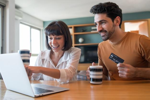 Porträt des jungen paares, das online mit einer kreditkarte und einem laptop von zu hause aus einkauft