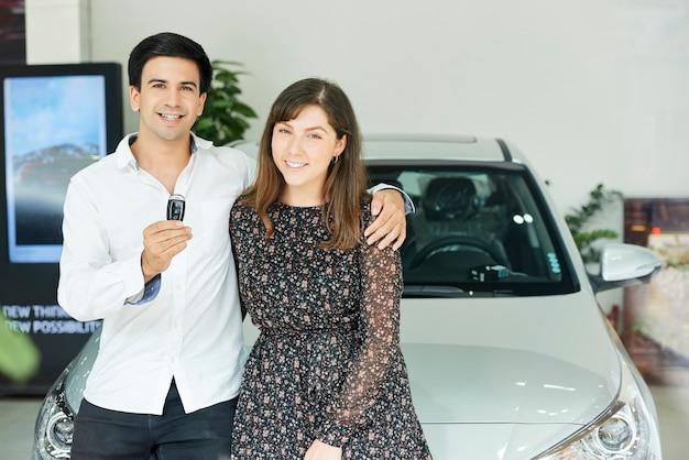 Porträt des jungen paares, das schlüssel von ihrem neuen auto hält, während sie im autohaus stehen, das umarmt und lächelt