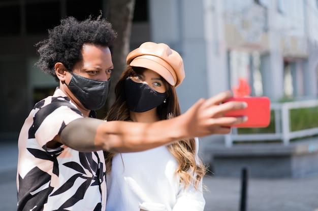 Porträt des jungen paares, das schutzmaske trägt und ein selfie mit handy während des gehens im freien nimmt