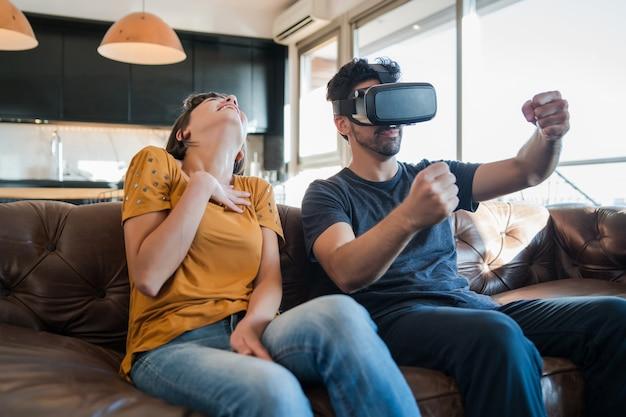 Porträt des jungen paares, das spaß zusammen hat und videospiele mit vr-brille beim sitzen spielt