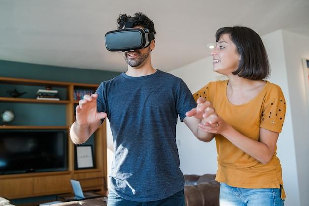 Porträt des jungen paares, das spaß zusammen hat und videospiele mit vr-brille spielt, während zu hause bleibt. neues normales lifestyle-konzept.