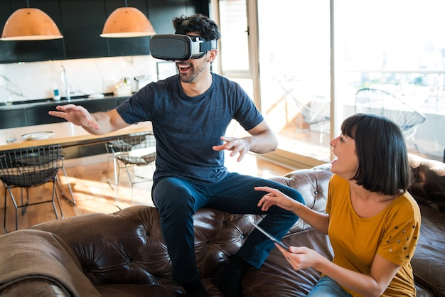 Porträt des jungen paares, das spaß zusammen hat und videospiele mit vr-brille spielt, während zu hause bleibt