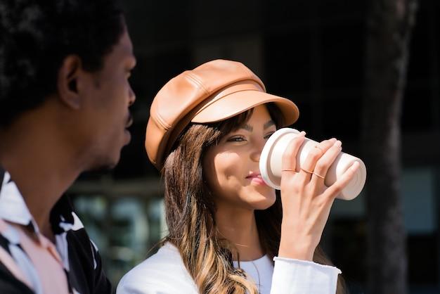 Porträt des jungen paares, das zeit zusammen verbringt und kaffee trinkt, während man draußen sitzt. stadtkonzept.