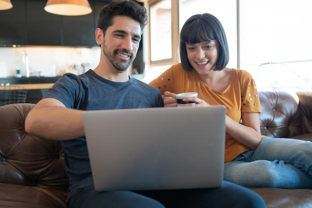 Porträt des jungen paares, das zeit zusammen verbringt und laptop beim sitzen auf der couch zu hause verwendet.