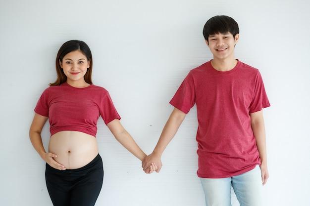 Porträt des jungen paares. gut aussehender ehemann und schwangere frau lächelnd stehend halten hand glücklich vor weißem hintergrund. sie erwarten ein gesundes baby.