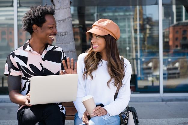 Porträt des jungen paares unter verwendung des laptops, während draußen auf der straße sitzend