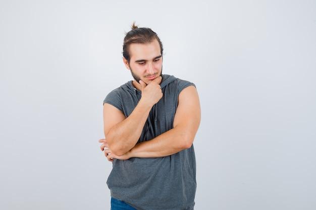 Porträt des jungen passenden mannes, der in der denkenden haltung im ärmellosen kapuzenpulli steht und nachdenkliche vorderansicht schaut