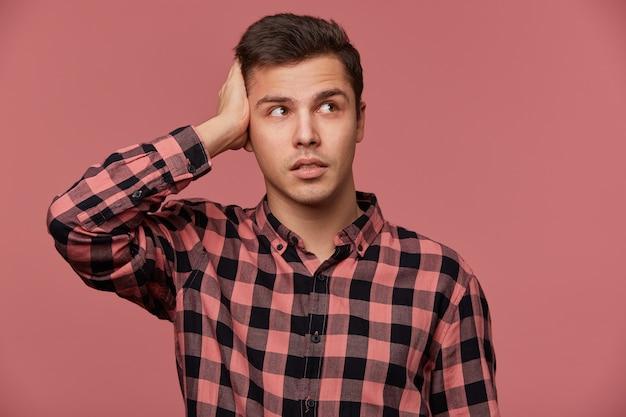Porträt des jungen pencive-mannes im karierten hemd, schaut weg, steht über rosa hintergrund und berührt kopf, sieht müde und traurig aus.