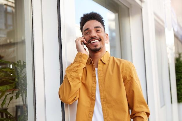 Porträt des jungen positiven afroamerikaners, der die straße entlang geht und am telefon spricht