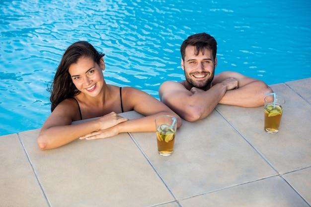 Porträt des jungen romantischen paares, das im pool entspannt