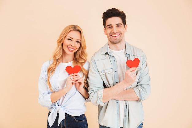 Porträt des jungen romantischen paares mann und frau in der grundkleidung lächelnd und hält zwei rote papierherzen, lokalisiert über beige wand