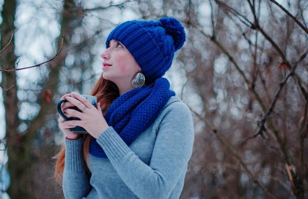 Porträt des jungen roten haarmädchens mit den sommersprossen, die an der blauen strickmütze und am schal mit tasse tee am wintertag tragen.