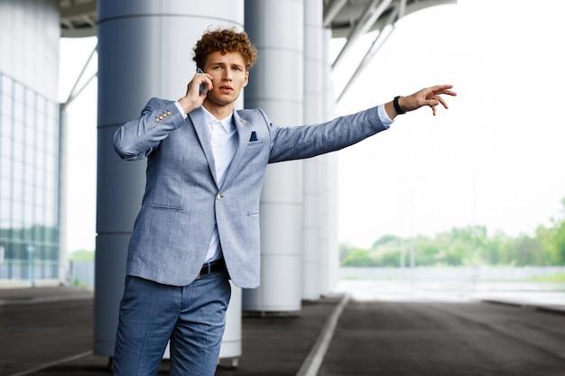 Porträt des jungen rothaarigen geschäftsmannes, der das auto fängt und am telefon spricht