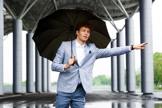Porträt des jungen rothaarigen geschäftsmannes, der das auto fängt und regenschirm hält