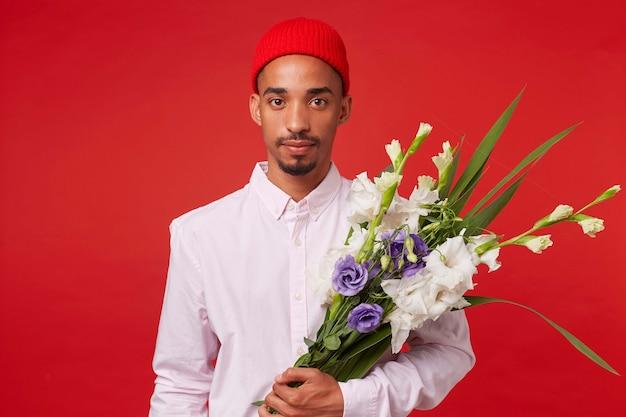 Porträt des jungen ruhigen afroamerikanischen mannes, trägt im weißen hemd und im roten hut, schaut in die kamera und hält blumenstrauß, steht über rotem hintergrund.