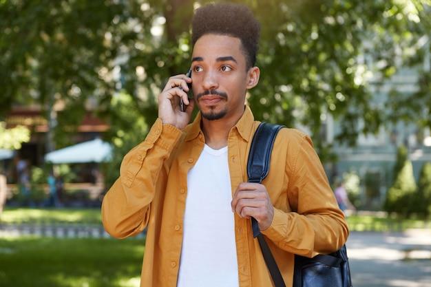 Porträt des jungen ruhigen dunkelhäutigen mannes im gelben hemd, der auf dem park geht, telefon hält, antwort von seiner freundin wartet, sieht nachdenklich.